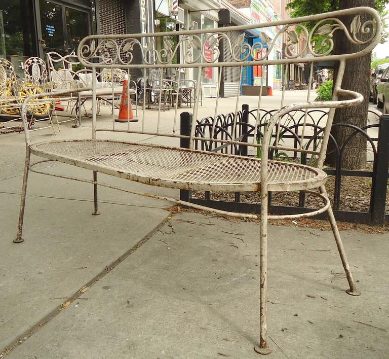 Pair of outdoor benches in iron. Each love seat has a strong frame with curving arms, slat backs and decorative leaf trim.  (Please confirm item location, NY or NJ, with dealer).