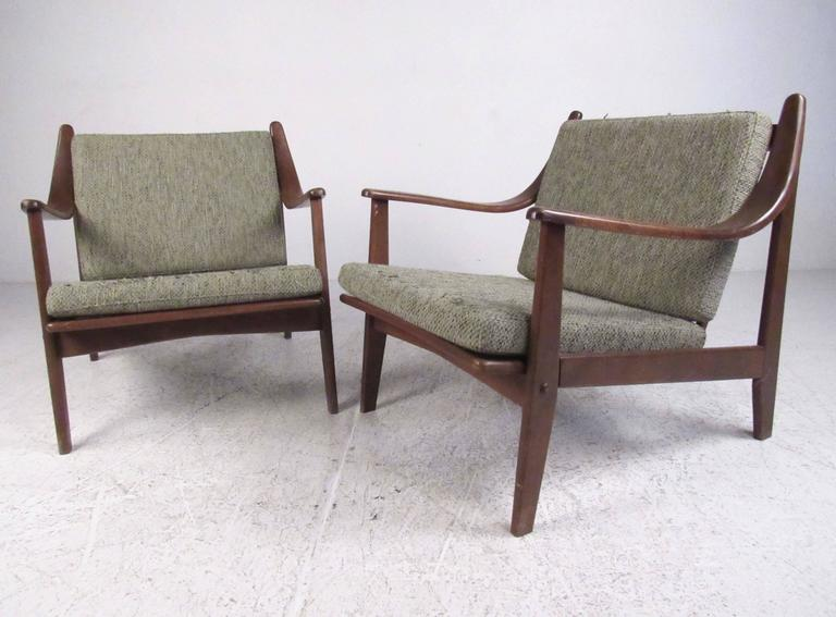 This stylish pair of Mid-Century Modern lounge chairs feature sculpted walnut construction with comfortable vintage upholstery. Spingle backs and unique sloped arm rests add to the Danish modern Finn Juhl style of the pair. Please confirm item