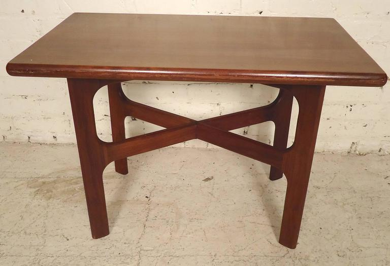 Simple and elegant end table with walnut grain and sculpted legs. Attractive cross bar design.