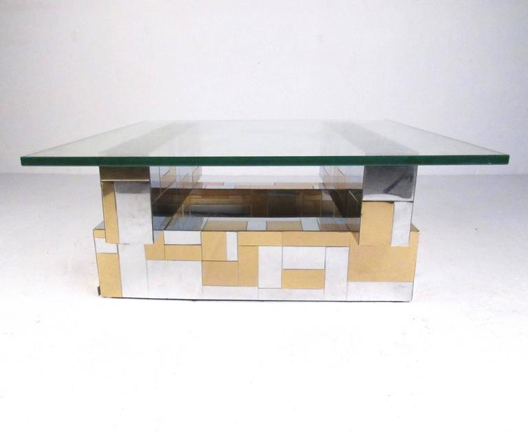 This stylish Mid-Century Modern Paul Evans coffee table features his iconic Cityscape design with patchwork chrome and brass finish. Thick glass tops a stylish four piece base and makes an impressive center table in any seating area. Please confirm