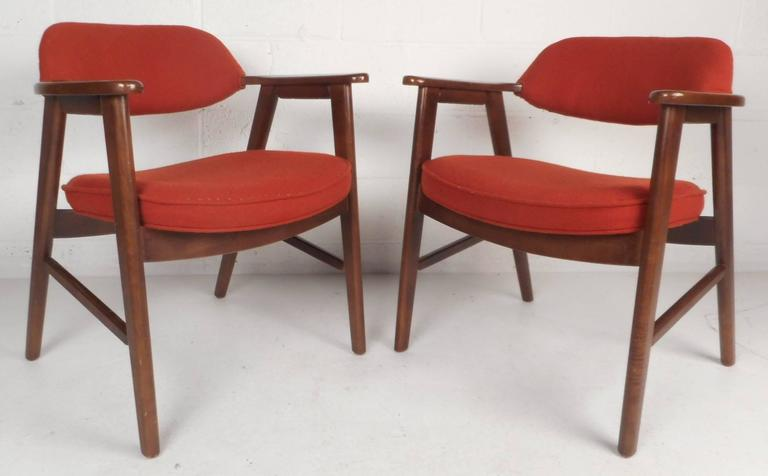 This beautiful pair of vintage modern side chairs feature a solid dark mahogany frame and plush red upholstery. Unique design has stylish cut-out arm rests and angled back legs. This sleek and sturdy Mid-Century Modern pair of arm chairs make the
