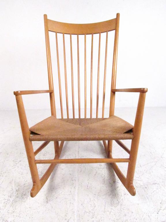 This stylish Mid-Century rocking chair features tall beech frame with shapely spindle back and comfortable rush seating. The iconic design of this Scandinavian modern J.16 rocking chair is credited to Hans Wegner and makes a striking impression in