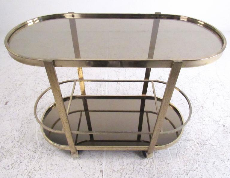 This stylish modern bar cart features oxidized brass finish with two tier oval shelves for storage and display. Mirrored glass bottom and Mid-Century style make this a versatile and attractive cart for bar service or storage. Please confirm item