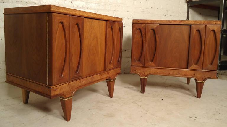 This pair of gorgeous night stands by American of Martinsville features rich walnut grain, brass accents on two of the four sturdy legs, two doors, and a spacious storage unit with one drawer.
