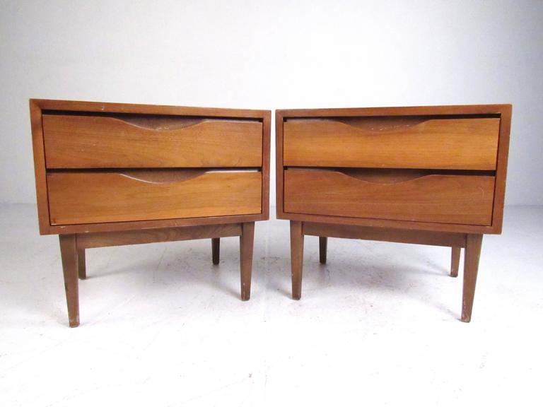 This vintage modern pair of walnut nightstands make a stylish retro addition to any bedroom. Perfect height for bedside storage, but two spacious drawers offer plenty of space for any interior setting. Please confirm item location (NY or NJ).