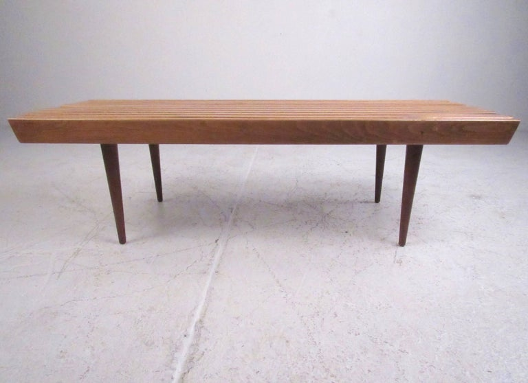 This stylish vintage coffee table features slat walnut construction and tapered hardwood legs. The sturdy Mid-Century construction makes this a perfect choice for living room coffee table or for use as a bench for occasional seating. Please confirm
