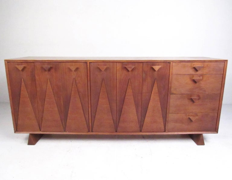 This stunning and unique bedroom set features sculpted walnut construction with unique Nakashima style design. Triangular wedge legs, drawer pulls, and carved details add to the Mid-Century Modern appeal of the matching five piece set. Sculpted