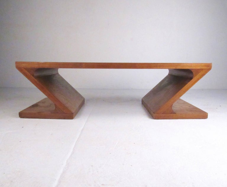 This uniquely shaped vintage modern coffee table by Lane features two-tone oak marquetry with stylish Z type design. The vintage modern appeal of the coffee table makes it an impressive addition to any seating area. Pair of matching end tables also
