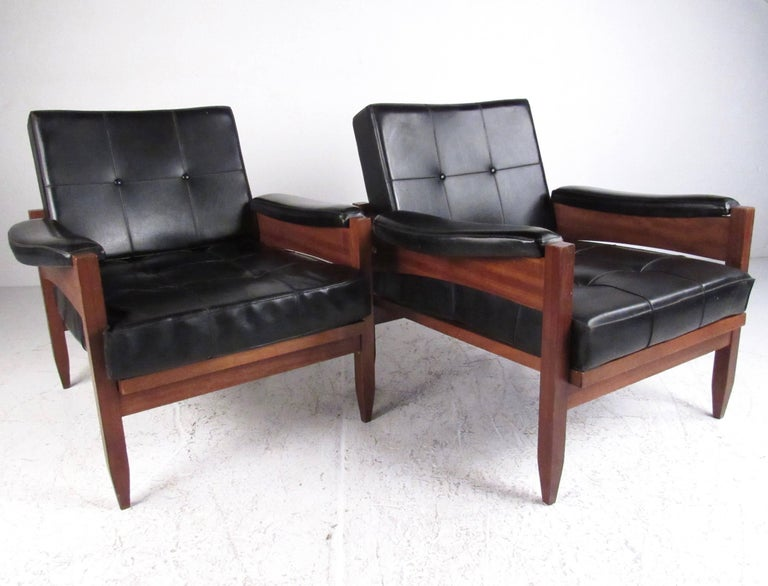 This stylish pair of Mid-Century club chairs feature tufted vinyl upholstery with sturdy teak frames. The vintage modern appeal of the stylish Scandinavian pair make a comfortable and impressive seating addition to any interior. Please confirm item