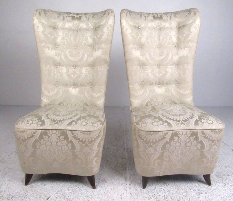 This stunning pair of elegant slipper chairs feature Mid-Century, Italian modern style similar to the style of Paolo Buffa. The sculpted high back seats feature ornate vintage upholstery, braided piping and tufted seats. The hardwood tapered legs