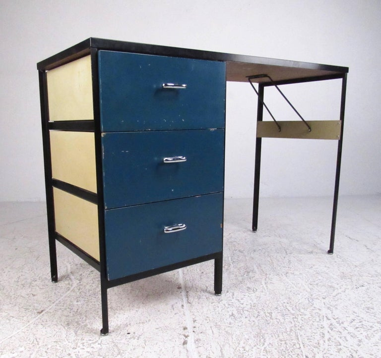 This iconic Mid-Century Modern writing desk features steel frame design with brightly painted drawers. Unique vintage design by George Nelson for Herman Miller makes the perfect workspace addition to any home or business office. Please confirm item