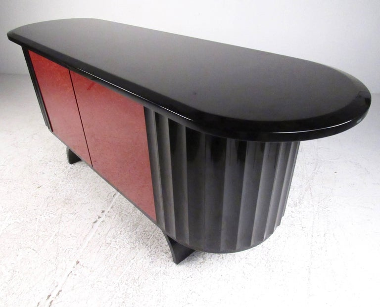 This stunning sculptural credenza features exotic wood doors with a gloss black lacquer finish. Unique base and fantastic shape make this storage cabinet the perfect modern deco addition to home or business. Please confirm item location (NY or NJ).