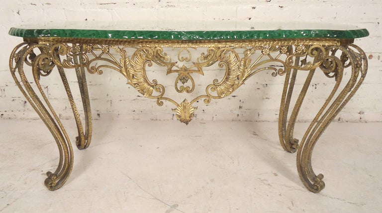 Beautiful Italian table made of hammered bronze with a thick chiselled glass top. Unique decorative flair on base with scrolling legs.  (Please confirm item location - NY or NJ - with dealer).