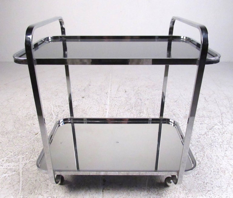 Offering plenty of room for storing glassware and bottle, this Mid-Century chrome and glass service cart makes a stylish and versatile addition to home or business. Top shelf is made of smoked glass, bottom has a mirrored finish. An impressive