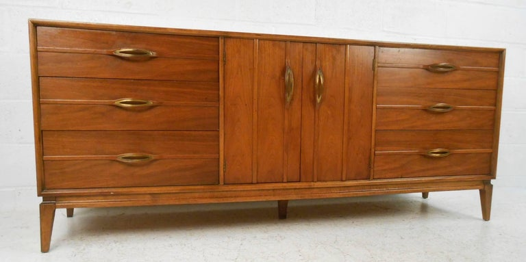 This gorgeous vintage modern dresser features unusual sculpted pulls on each drawer and cabinet. Sleek design provides plenty of room for storage within its nine hefty drawers. Sturdy construction with stunning walnut wood grain and splayed legs.
