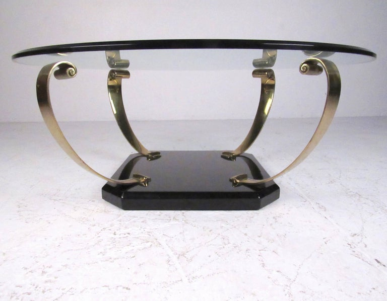 This stylish vintage coffee table features scrolled brass arms mounted on a black lacquer base with a bevelled glass top. Impressive Regency style makes a striking addition to home or business, please confirm item location (NY or NJ).