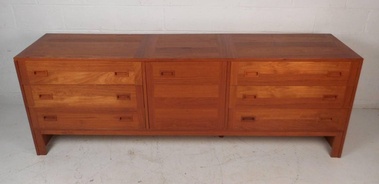 This beautiful vintage modern sideboard features an abundance of storage space within its six hefty drawers and compartment behind a cabinet door. Elegant teak wood grain and unique rectangular recessed drawer pulls add to the Mid-Century appeal.