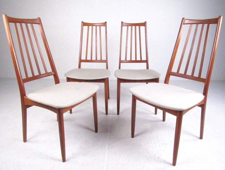 This sleek and slender set of four teak dining chairs feature statuesque high back design with sculpted spokes. Upholstered seats strike a nice contrast with the rich teak finish while tapered legs round out theMid-Century Modern style of this