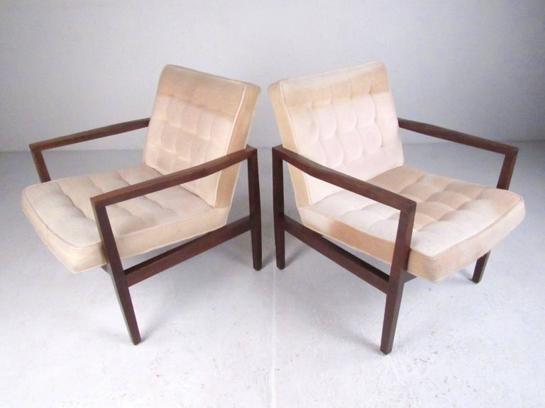 This stylish pair of vintage modern club chairs feature cubist style solid walnut frames with tufted vintage upholstery and comfortable proportions. Perfect pair of matching lounge chairs for home or business seating. Please confirm item location