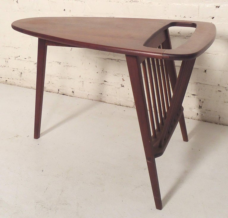 Fun midcentury design by Umanoff featuring a triangle top end table set on three legs. Deep walnut grain and spindle magazine rack.  (Please confirm item location - NY or NJ - with dealer).