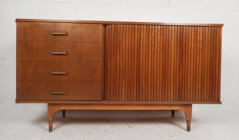 This gorgeous vintage modern credenza features six hidden drawers behind a cabinet and a tambour door. Unique cabinet door has appearance of four faux drawers with sculpted metal pulls. Sleek compact design has tapered legs with brass trim around