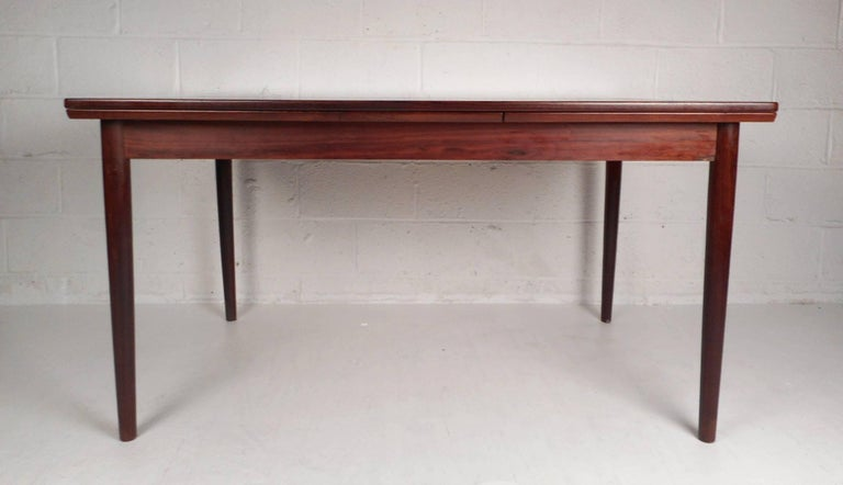 This beautiful vintage modern dining table features the ability to extend all the way to 97.5 inches wide from the original width of 55 inches. Elegant rosewood wood grain throughout and tapered legs add to the allure. Sleek design with hidden