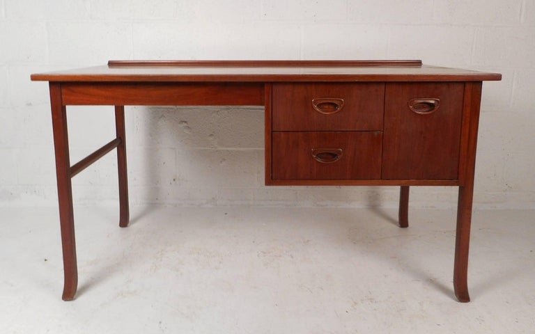 This gorgeous vintage modern desk features a unique raised top along the back and sculpted feet. Sleek design with unusual recessed pulls and a wonderful vintage teak finish. This case piece ensures plenty of room for storage within its three hefty