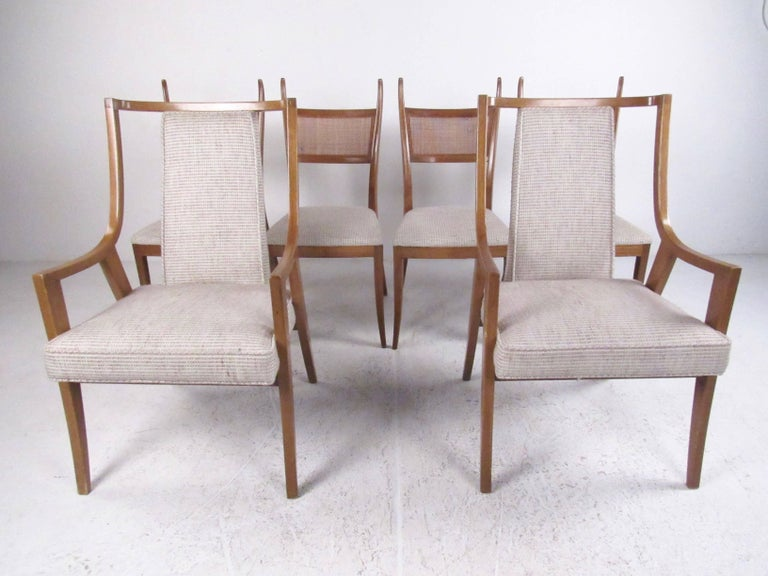This stylish set of midcentury dining chairs features the unique sculptural design of Harvey Probber, making a comfortable yet stylish addition to any dining room setting. Four matched side chairs are paired with two sleek mahogany armchairs. The