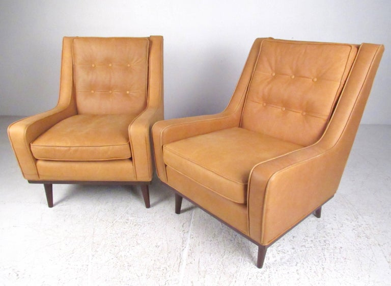 This beautiful pair of stylish leather club chair feature modern tapered legs, sleek low profile armrests, and spacious comfortable seats. Please confirm item location (NY or NJ).