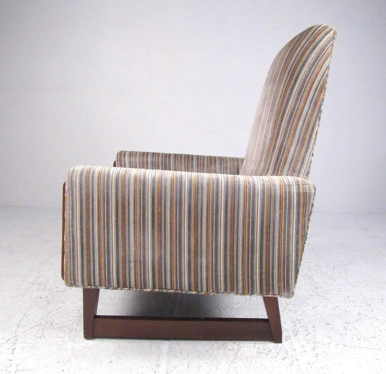 This unique vintage lounge chair features a high sculpted back, unique walnut trim, and vintage striped fabric. Sled style legs add to the Mid-Century Modern appeal of this Adrian Pearsall style chair. Please confirm item location (NY or NJ).