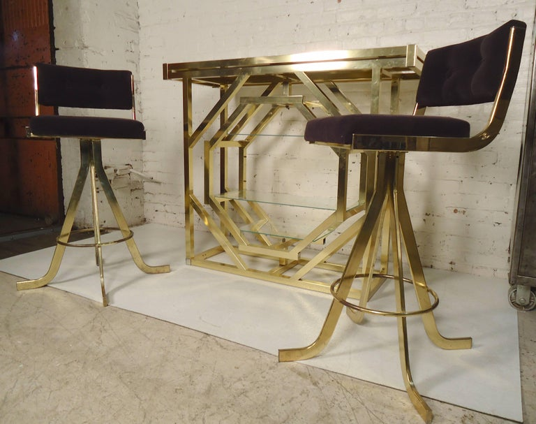 Beautiful brass dry bar with two stools. Bar has a black glass top and unusual rotating shelving unit. Stools have soft purple fabric.