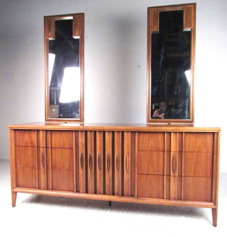 This beautiful six piece bedroom set features sculpted American modern design with unique handles. Matching suite offers plenty of storage space with highboy and lowboy, pair of nightstands, and two dressing mirrors. Unique midcentury design, please