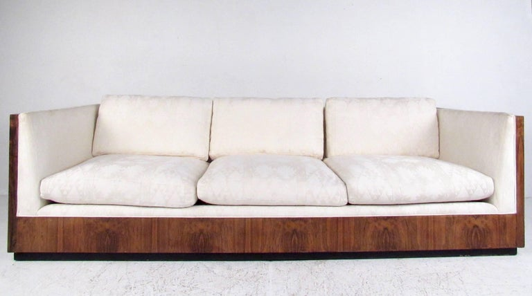 This stunning midcentury sofa features iconic Milo Baughman design for Thayer Coggin, featuring rosewood shell, wonderful vintage fabric, and comfortable seating for home or office. Original vintage condition includes manufacturing tag, please