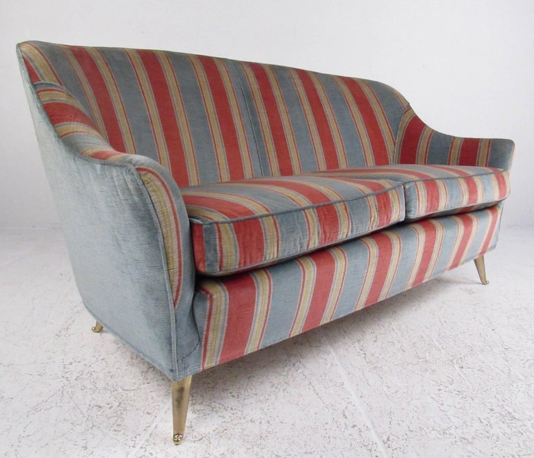 This stunning Italian modern sofa features Gio Ponti style, lovely vintage fabric, tapered brass legs, and comfortable upholstery. The beautiful loveseat makes an impressive midcentury addition to home or office, matching pair of lounge chairs also