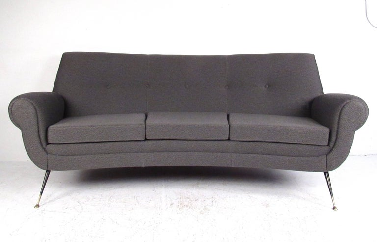This stunning three-seat sofa features sculpted seat back and armrests, designed by Gigi Radice. Featuring tapered brass legs, comfortable seating proportions, and newer tufted fabric. Stylish pair boasts rolled arms and splayed black enameled legs