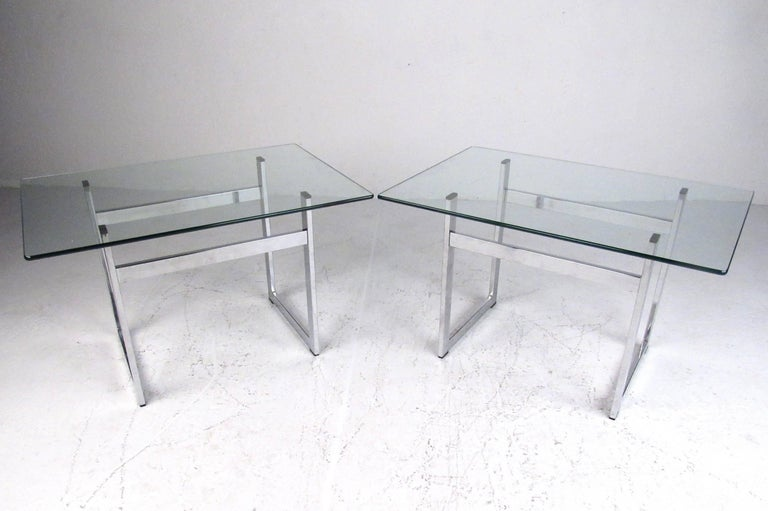 Stylish pair of contemporary modern end tables feature heavy chrome frame construction, rectangular glass tops, and unique midcentury style. Perfect addition to home or office, this matching pair make great lamp tables, sofa side tables, or display.