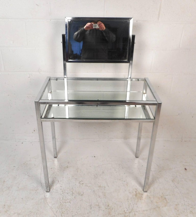 This beautiful vintage modern vanity features a heavy chrome frame with two tiers and a mirror. The unique design has a lower tier with a mirror top and a clear glass tabletop to set items on. Stylish console table with a mirror that swivels