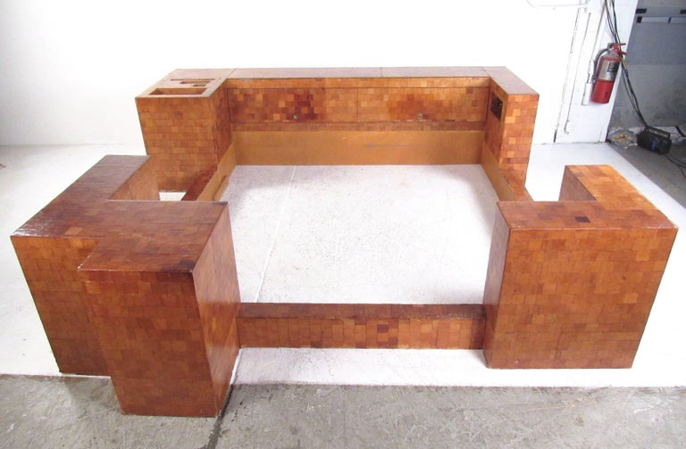 This large scale king-size bed frame features impressive custom design. Unique storage space in frame through various cubbys and cabinets, with original wiring awaiting your customizations. This multi-piece king size bed frame also features raisable