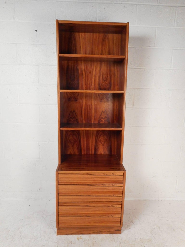 This beautiful vintage modern bookshelf features four wide shelves and five drawers on the bottom with sculpted pulls. This wonderful case piece offers plenty of room for storage while displaying items on the top. This versatile midcentury piece has