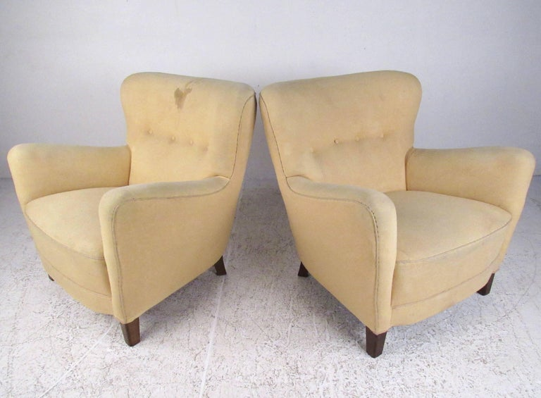 This stylish pair of shapely club chairs feature tufted upholstery make a comfortable addition to any seating area. The vintage appeal of this deco style pair makes for a warm and impressive addition to home or business seating. Please confirm item