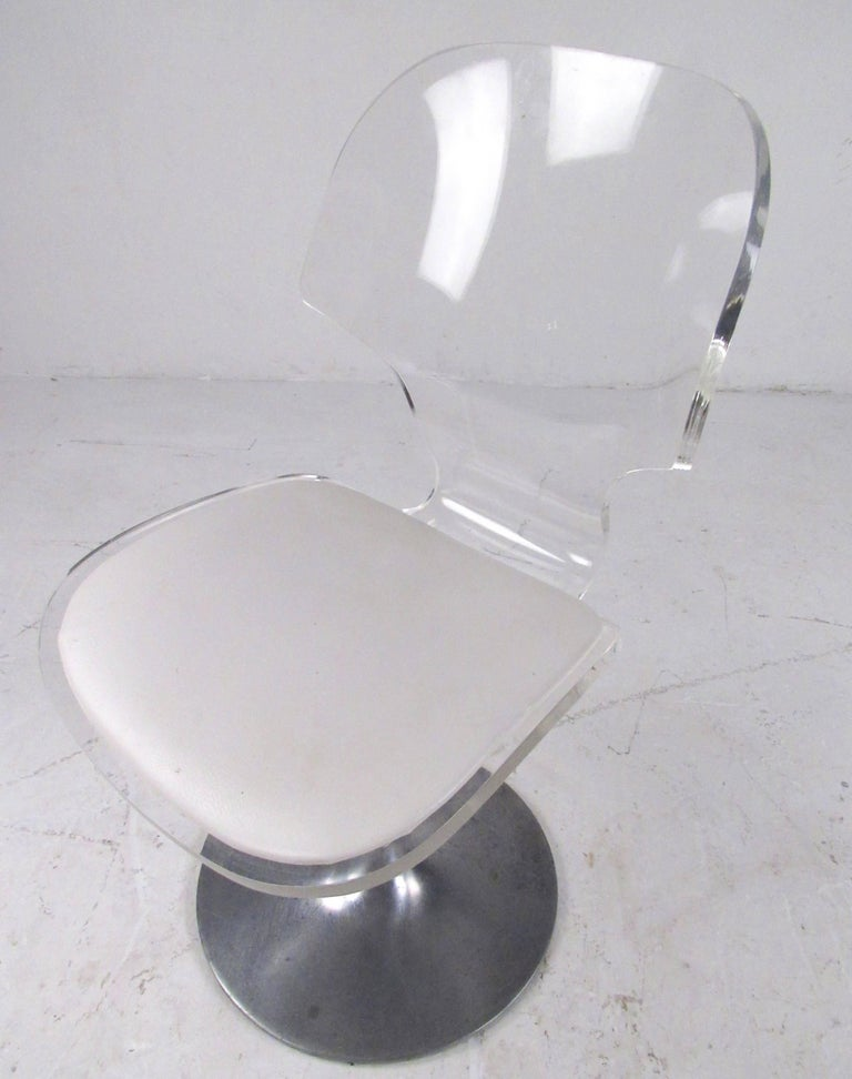 This Mid-Century Modern swivel side chair features Lucite frame with vinyl seat and unique aluminium tulip style base. The vintage design of the chair makes a simple yet elegant addition to home or business seating. Please confirm item location (NY