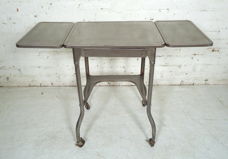Small side table restored in a bare metal style finish. Features a pair of drop leaf extensions. (Please confirm item location NY or NJ with dealer).