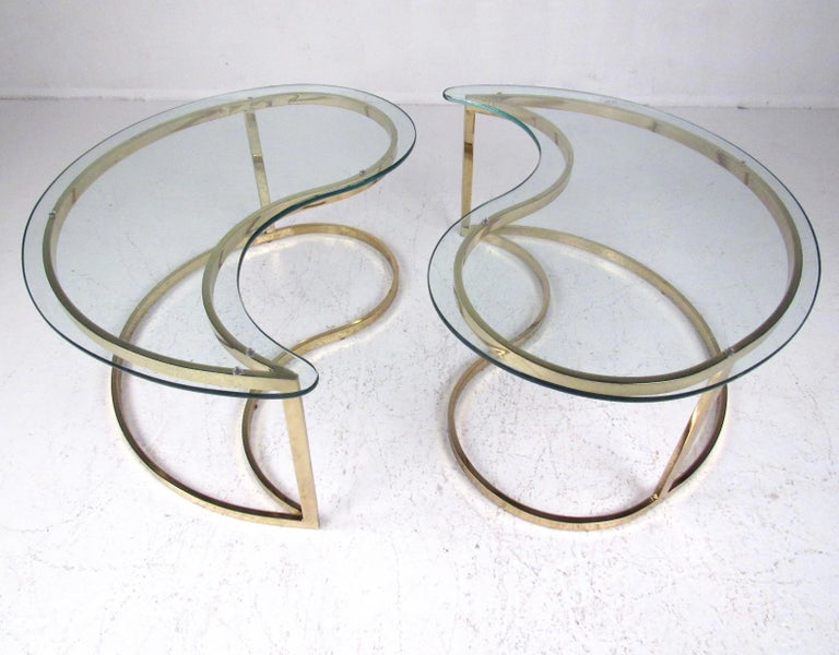 This pair of elegant modern end tables feature brass color finish and sculptural kidney shaped design. Thick glass tops make for perfect sofa end table or waiting room lamp table use. Please confirm item location (NY or NJ).