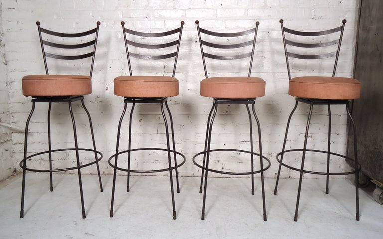 Set of Industrial stools featuring a slatted back, sturdy black iron legs and upholstered swivel seating.