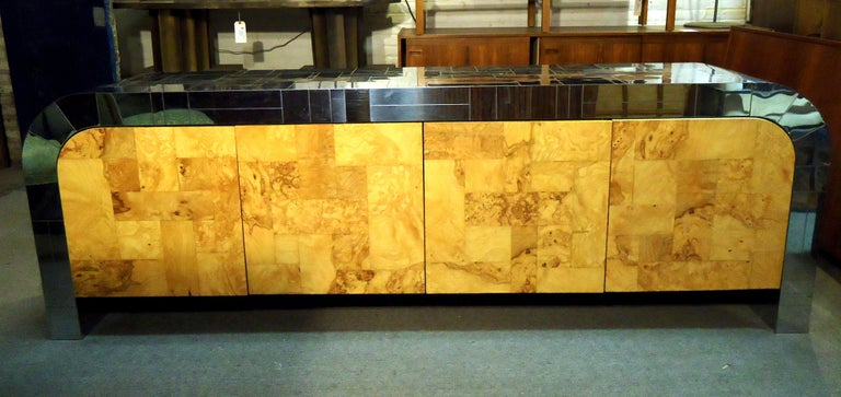 Gorgeous vintage modern Paul Evans credenza features spacious storage cabinets, three drawers, chrome top and sides, and burl wood doors. Signature is located on the inside foot underneath the cabinet.
