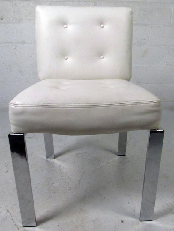 Vintage-modern dining chairs designed by Milo Baughman, features tufted white vinyl upholstery and sculpted chrome frame and legs.  Please confirm item location NY or NJ with dealer.