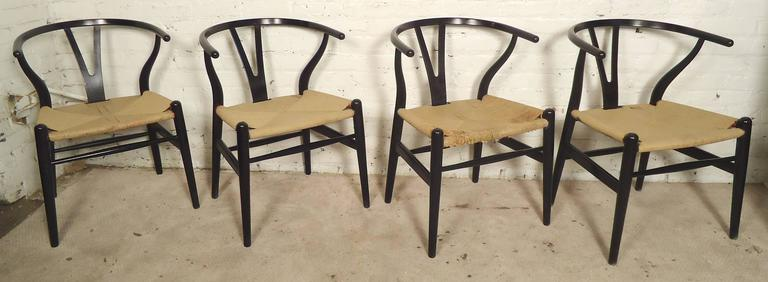Mid-Century Modern set by Hans Wegner refinished in black. Paper cord seats, sculpted frames,