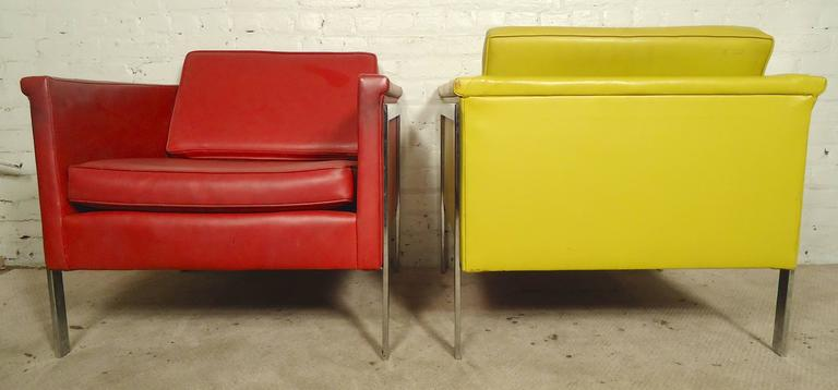 Striking pair of Mid-Century Modern lounge chairs with thick chrome legs that run across the side and back down, giving a nice modern profile. Colorful red and yellow vinyl upholstery make an impressive statement in home or business seating