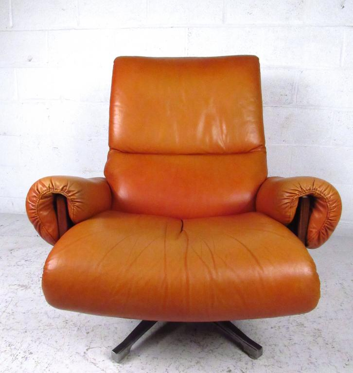 This unique and stylish pair of vintage swivel chairs features comfortable leather upholstery, ample padding on arm rests and seat back, and a low profile swivel tilt that adds even more comfort to the set. Rosewood frames show quality construction,