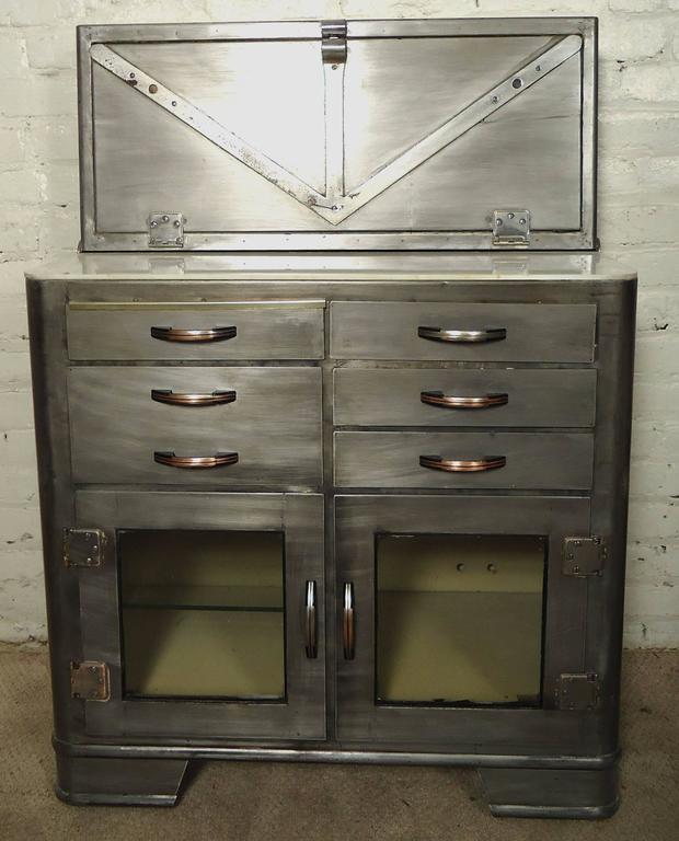 Industrial doctors cabinet, makes for a great modern kitchen or bathroom cabinet. Features drop down front with storage, bottom drawers and glass doors.  (Please confirm item location - NY or NJ - with dealer)
